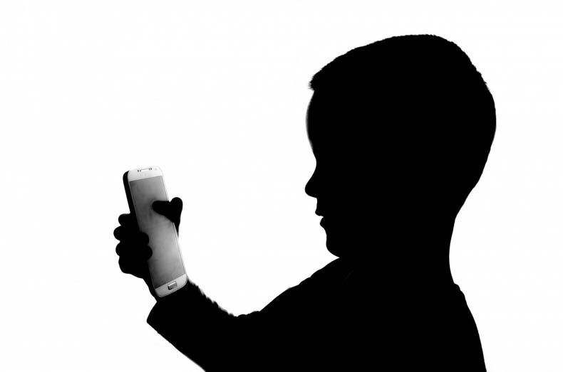 silhouette of child holding smartphone