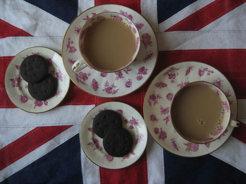 overhead view of teacups and girl scout cookies against a UK flag