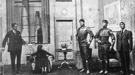 scene from play about robots, three robots on the right, man in a suit on the left
