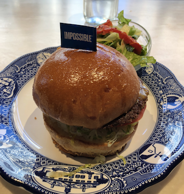 """A burger on a blue plate with a small flag that reads """"impossible"""""""